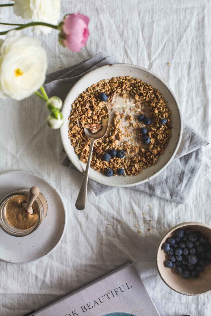 overhead image of a breakfast table setting on a textured white tablecloth. A bowl of almond butter maple granola sits int eh centre with a a small bowl of blueberries nearby and a jar of almond butter. Pink and white flowers in a vase off to the left.