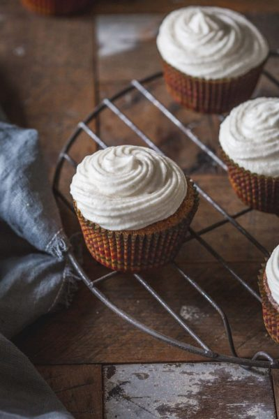 angled image of vegan pumpkin cupcakes on a cake rack
