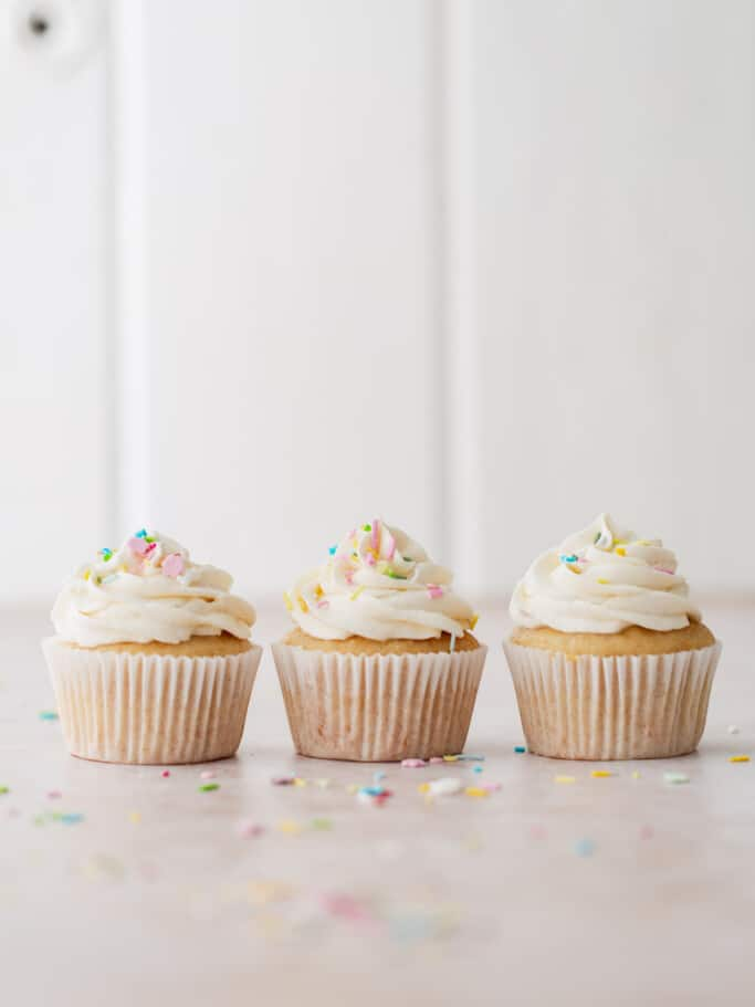 Three vanilla cupcakes in a row with sprinkles.
