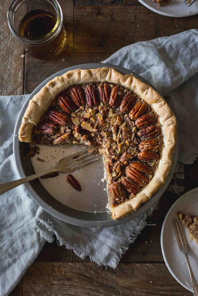 Close-up flat lay of cut into pecan pie in a pie pan