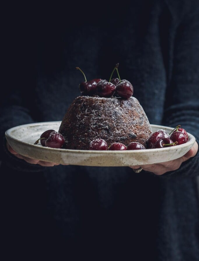 Woman holding a plate with a vegan Christmas pudding and cherries