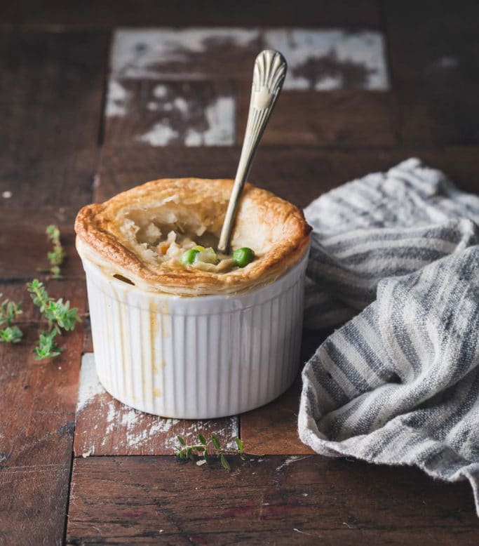 Close-Up of a Vegan Pot Pie in a white ramekin on a rustic wooden table
