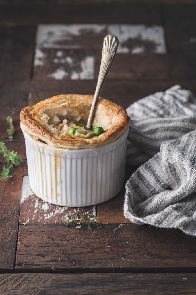 A vegan pie in a ramekin on a wooden table.