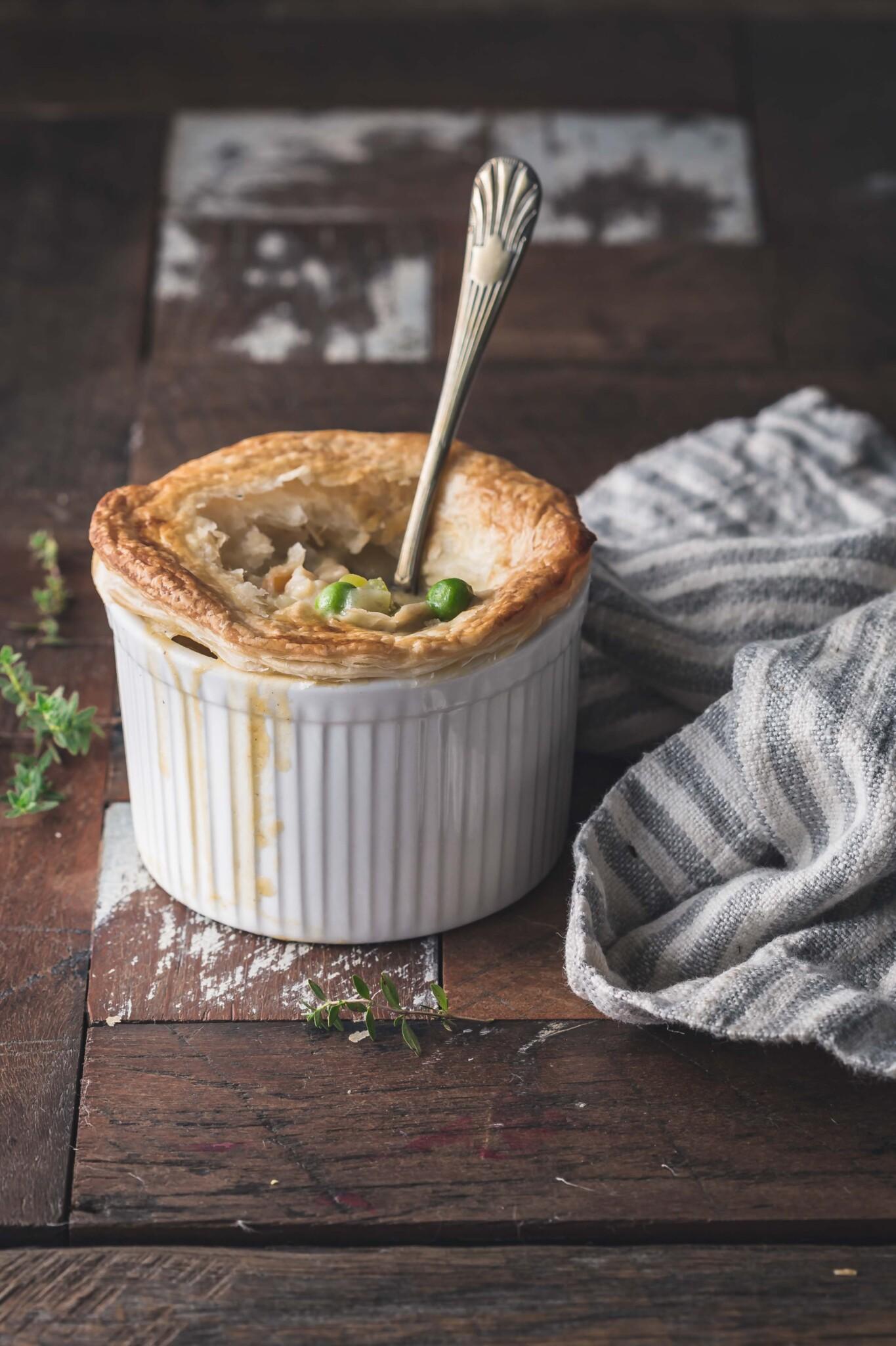 A vegan pot pie in a ramekin sitting on a wooden bench