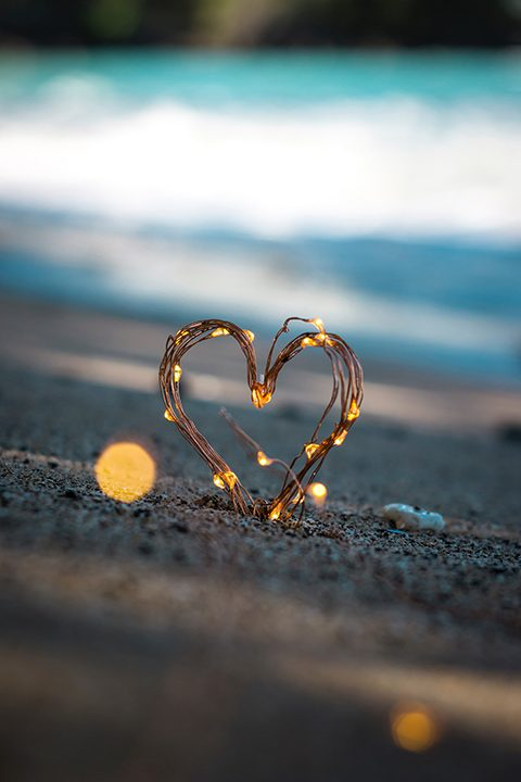 A close up of a wire heart in the sand