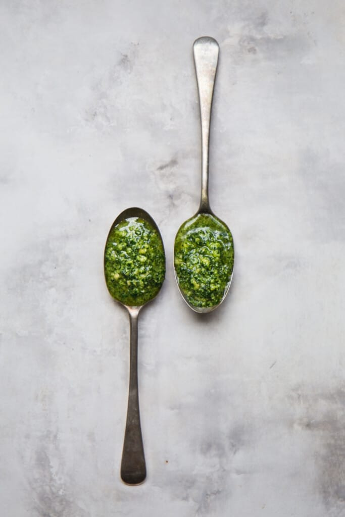 flat lay image of two rustic spoons filled with vegan kale pesto on a marbled tabletop