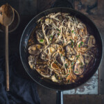 overhead image of a large skillet filled with spicy eggplant stir-fry on a rustic wooden table