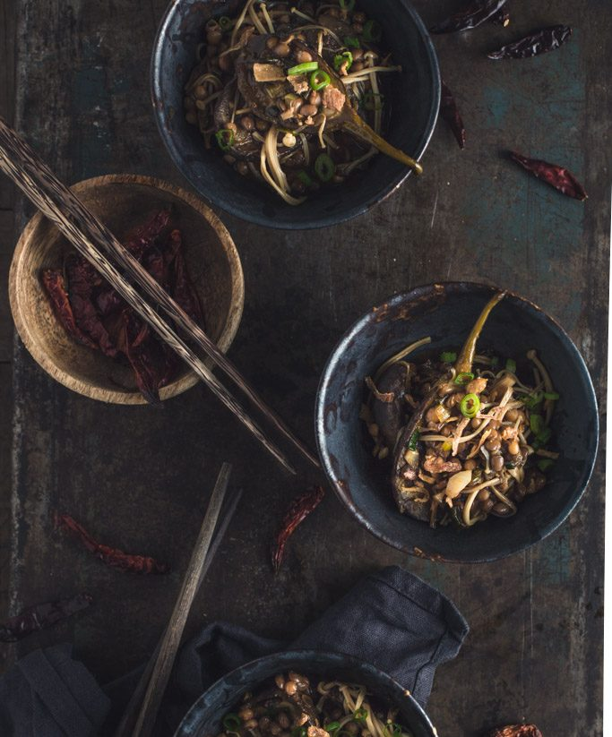 An overhead image of several small bowls of eggplant stir-fry on a rustic metal tabletop
