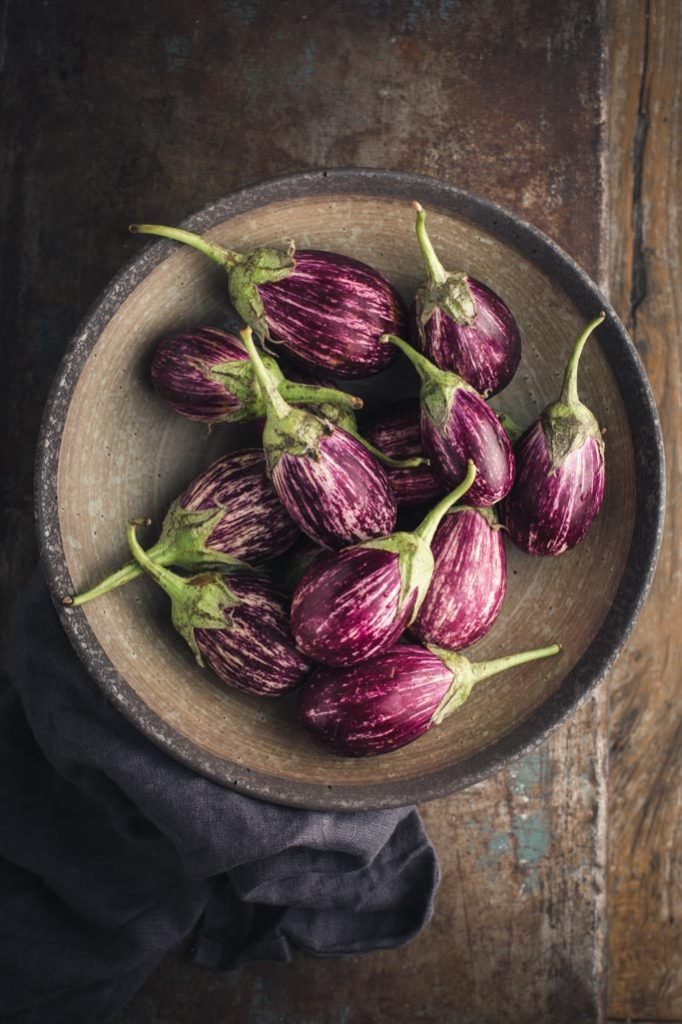 An overhead image of a bowl of the striped small eggplants used in the recipe