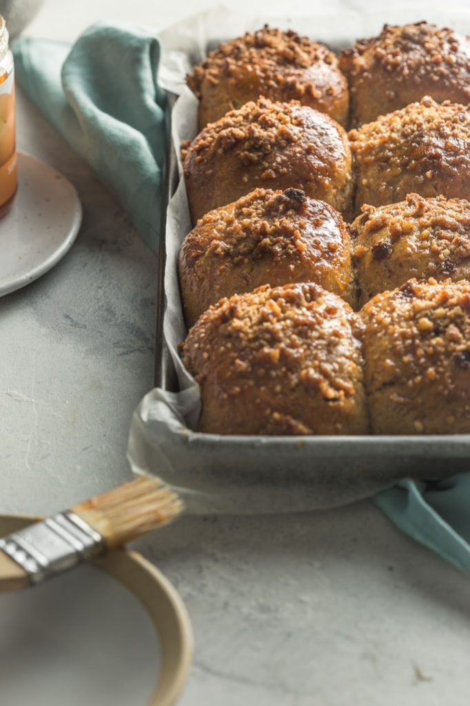 A close-up breakfast table setting with a tray of freshly baked vegan carrot Easter buns with walnut streusel set to the right side of the frame.