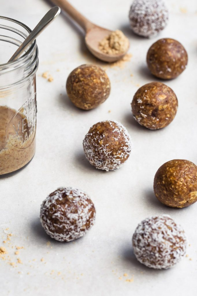 45 degree angle image of a cluster of almond butter oat energy balls with a jar of almond butter and a scoop of protein powder nearby