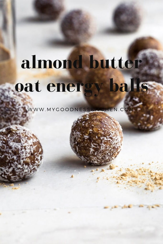Close up image of almond butter oat energy balls on a rustic white surface with title text overlay