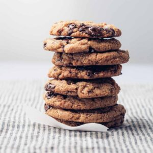 A stack of chocolate chip cookies on a striped napkin.