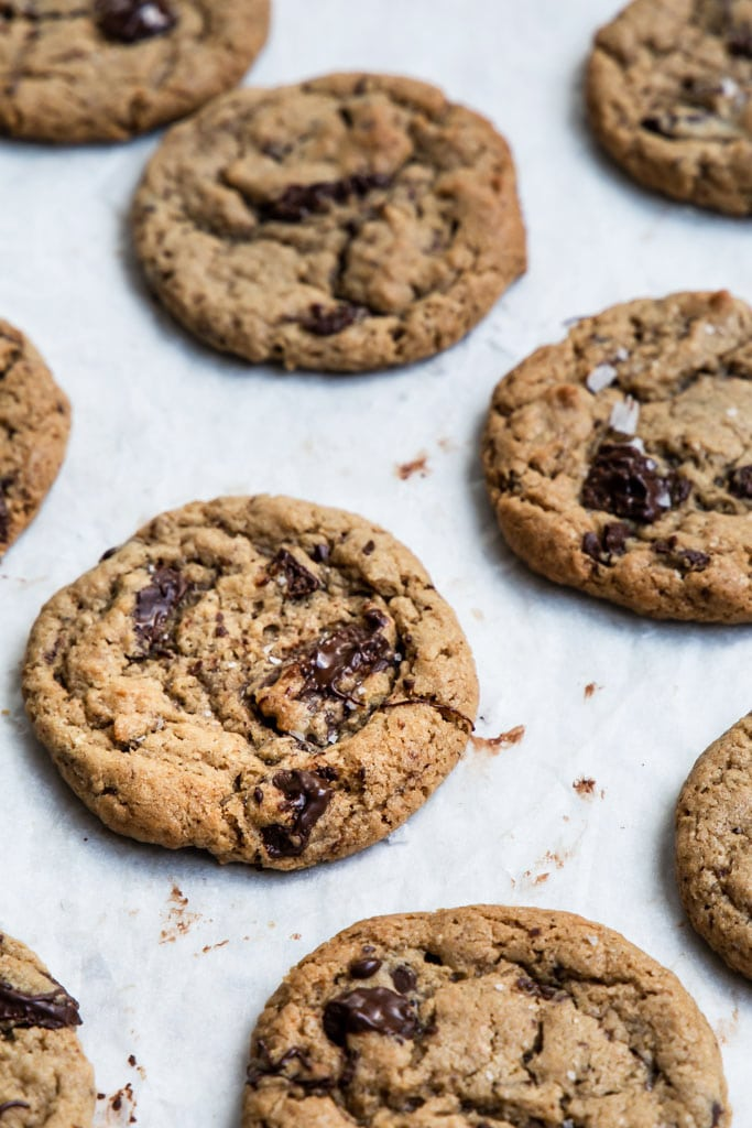 a close up image of freshly baked tahini chocolate chip cookies on white baking paper