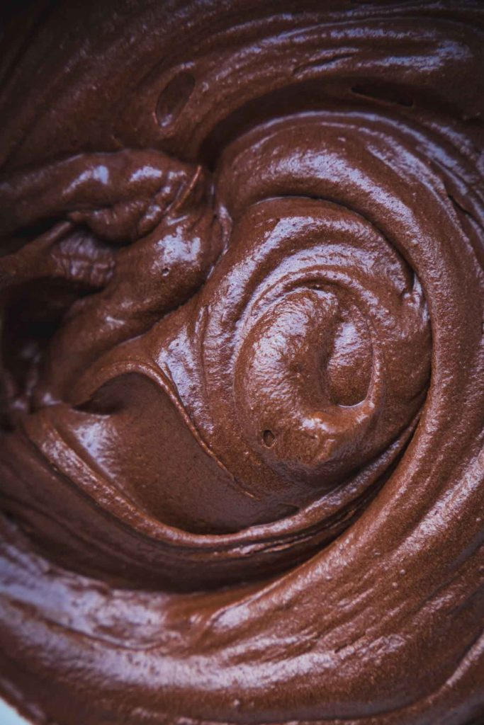 A super close full-frame image of swirls of chocolate frosting