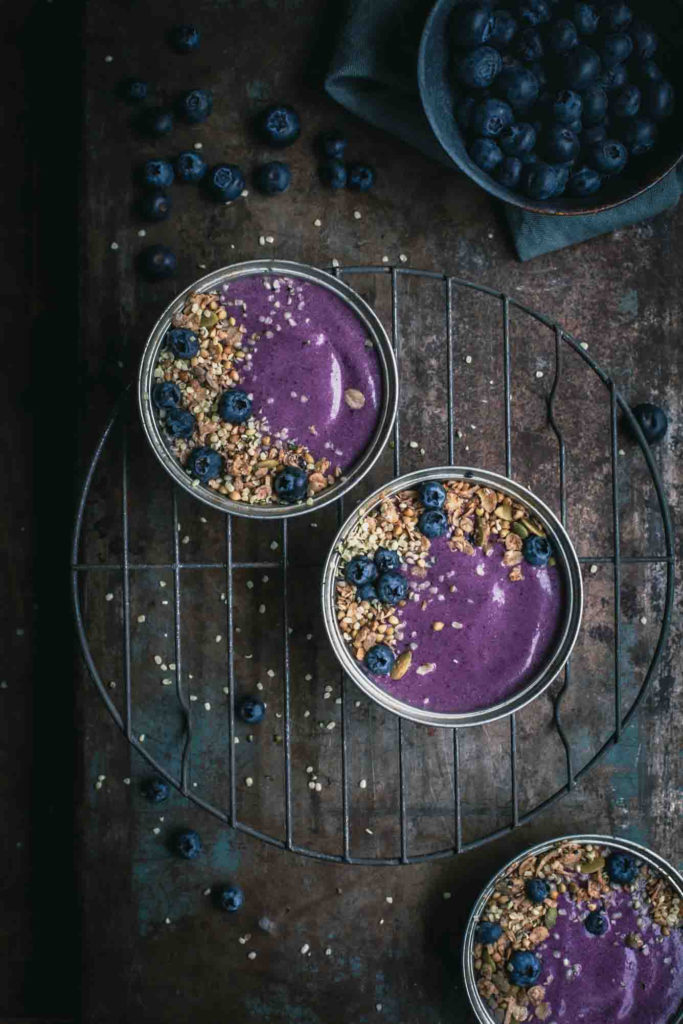 Overhead image of 3 small pie tins filled with thick blueberry pie smoothie, granola and fresh blueberries on a rustic table. A bowl of blueberries sitting off to the side.