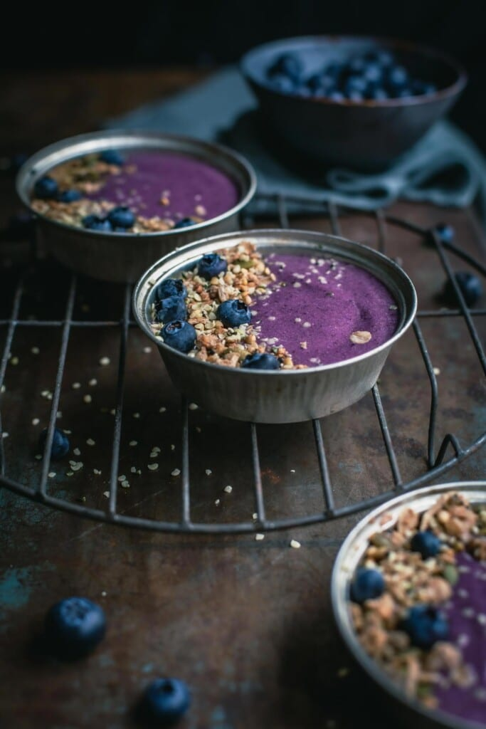 A 45-degree angle image of three small pie tins filled with thick blueberry pie smoothie, granola and fresh blueberries sitting on an old wire cake stand. A bowl of blueberries in the background.