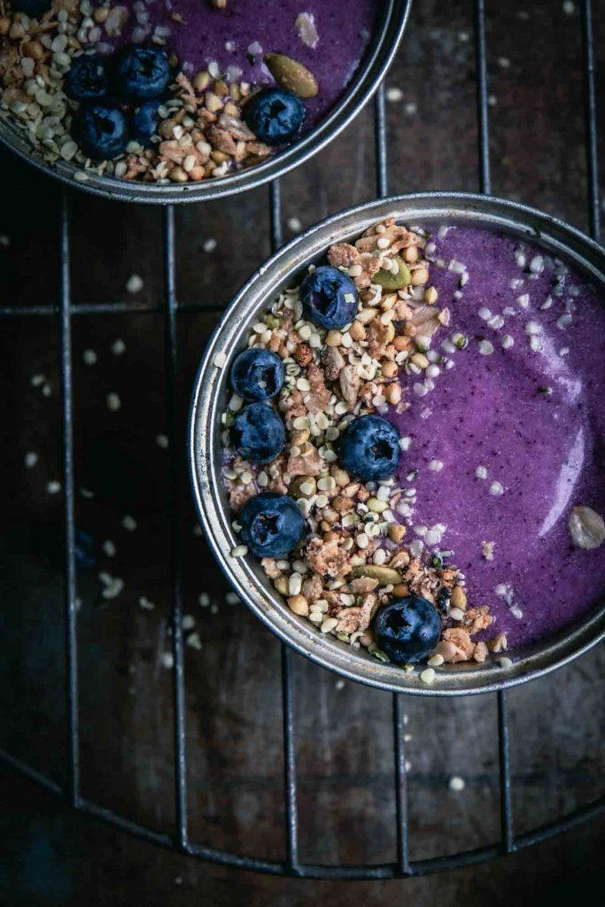 A super close-up image of a blueberry pie smoothie bowl served in a pie tin with granola and fresh berries.