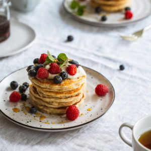 A close up of a plate of pancakes and berries on a table.