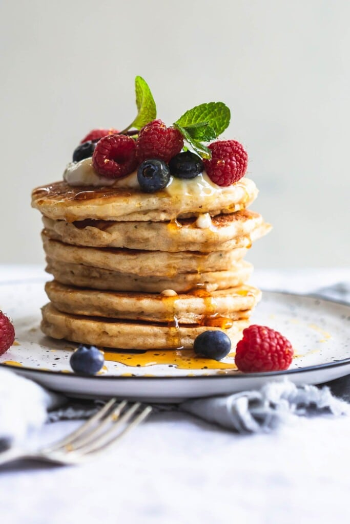 A close up, front on image of a stack of 6 whole wheat vegan pancakes topped with vegan yoghurt and berries sitting on black rimmed white plate with a crinkled napkin underneath.