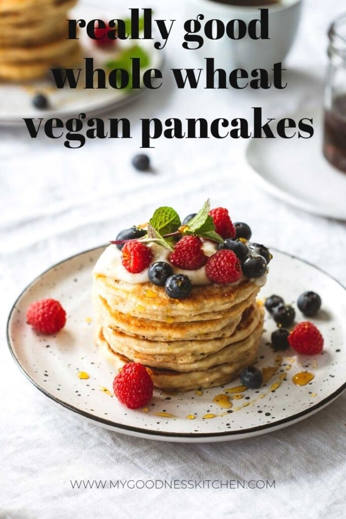 An angled image of a breakfast table setting with a stack of whole wheat vegan pancakes topped with vegan yoghurt and berries in the foreground. Another stack sits in the background next to a cup of coffee and a pot of maple syrup. Title text overlay.