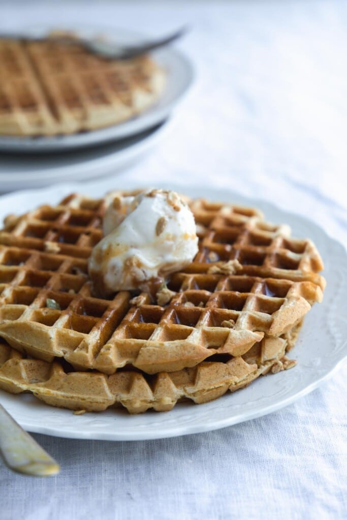 A close-up image of a serving of vegan pumpkin waffles on a white plate with ice-cream, granola sprinkles and maple syrup