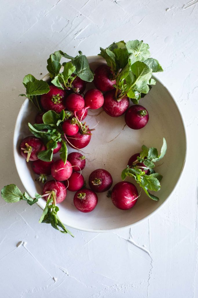 A wreath of freshly washes radishes with their leaves still attached in a rustic white bowl