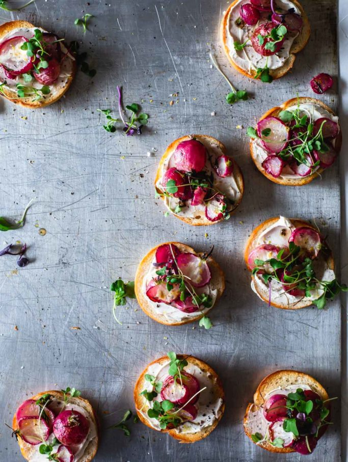 an overhead image of roasted radishes sitting on top of 6 mini bagels with cream cheese and micro greens on a metal tray