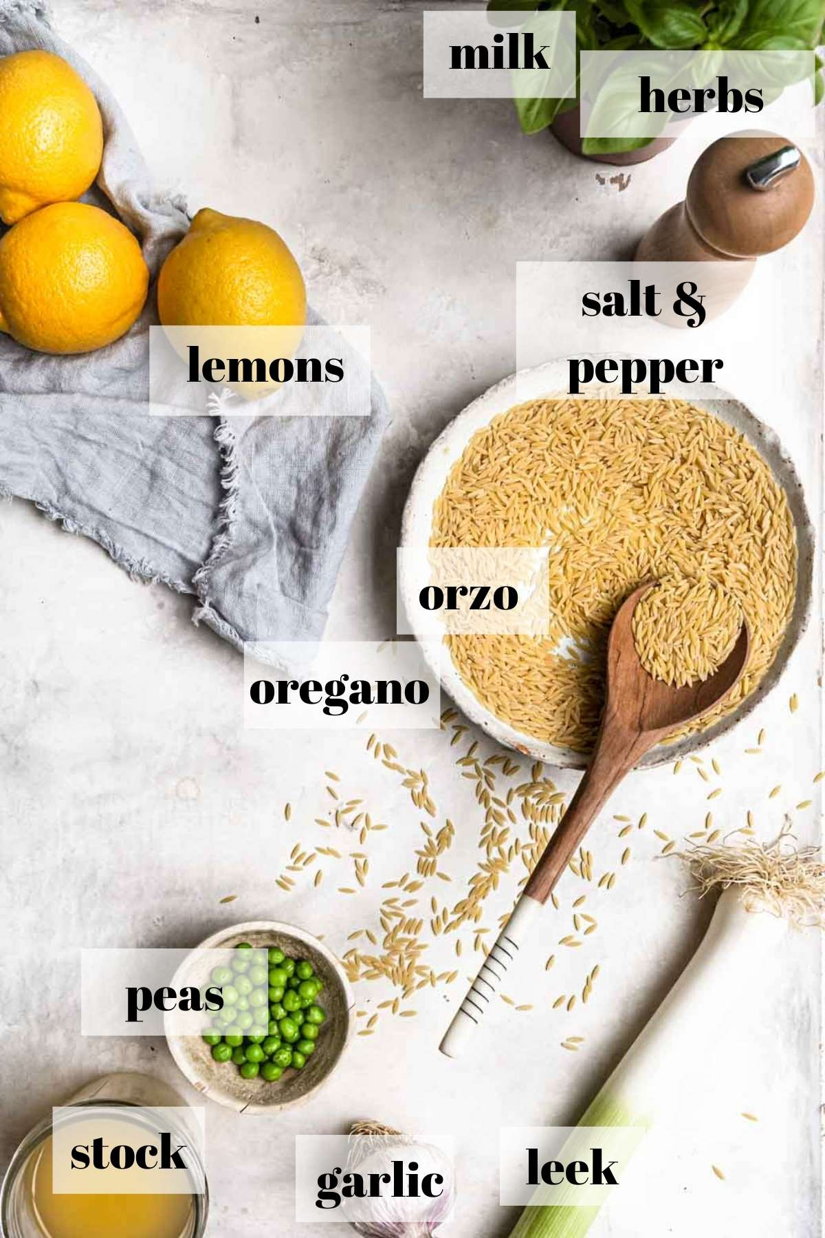 Lemon orzo ingredients labelled and laid out on a white table.