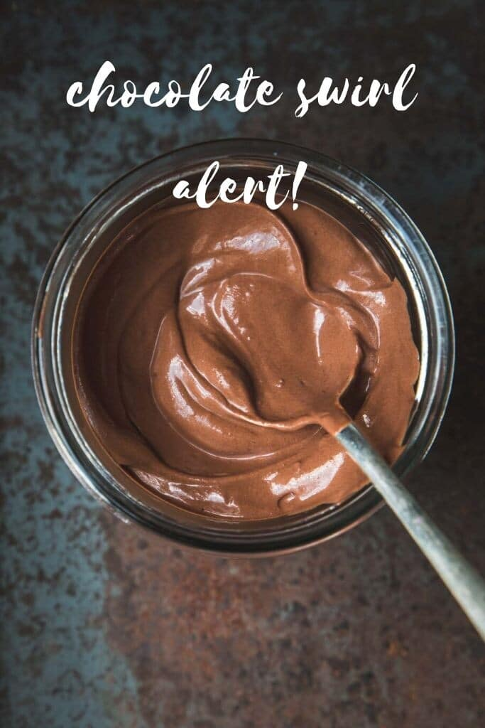 """Close-up overhead image of a large jar of vegan chocolate mousse swirled inside with a spoon sitting on an angle. The words """"chocolate swirl alert"""" is written in white."""