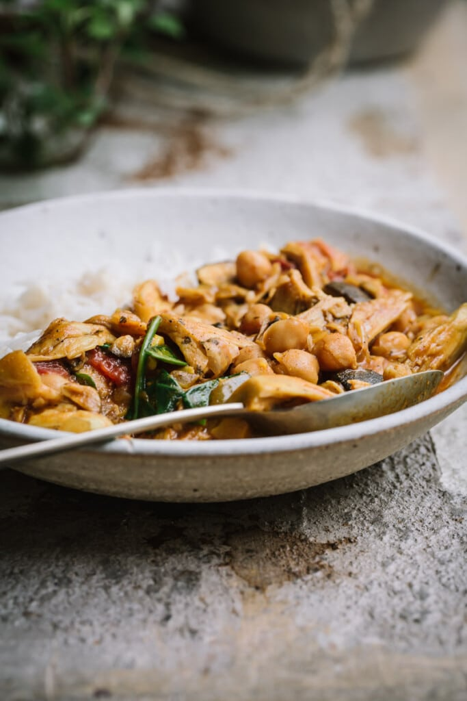 A close-up image of a clay bowl full of mushroom and chickpea tikka masala and rice on a rustic white table