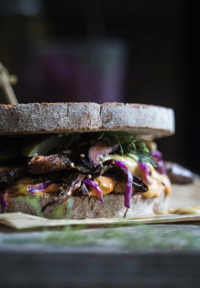 Close-up front on image of a finished vegan mushroom Reuben Sandwich sitting on brown baking paper