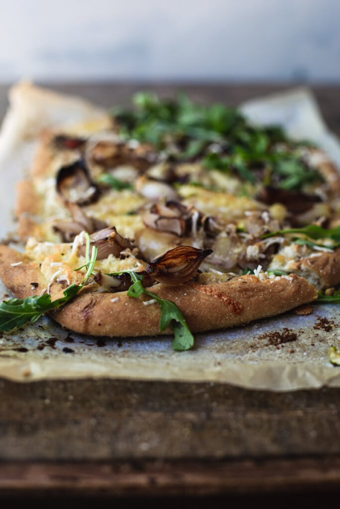 A front on image of a rustic vegan white pizza with pear and balsamic shallots sitting baking paper on a rustic wooden board. Green rocket is sprinkled over the pizza.