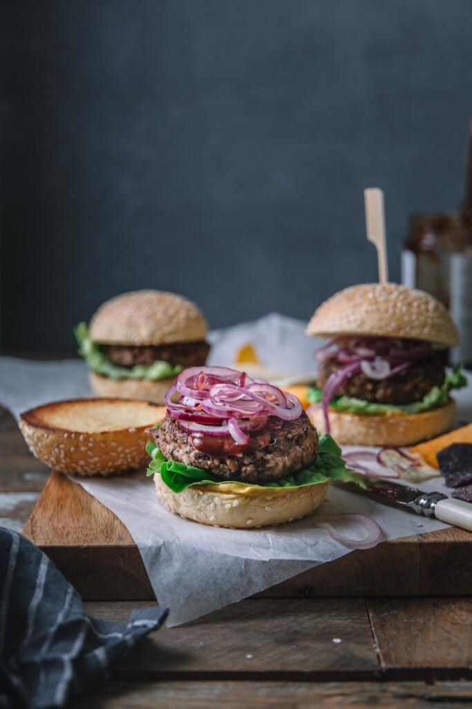 Image shot from the front of 3 BBQ vegan black bean burgers on a wooden board with parchment payment on top. The front centre burger is in focus and has its top burger bun set aside to show the burger, BBQ sauce and fried onions on top.