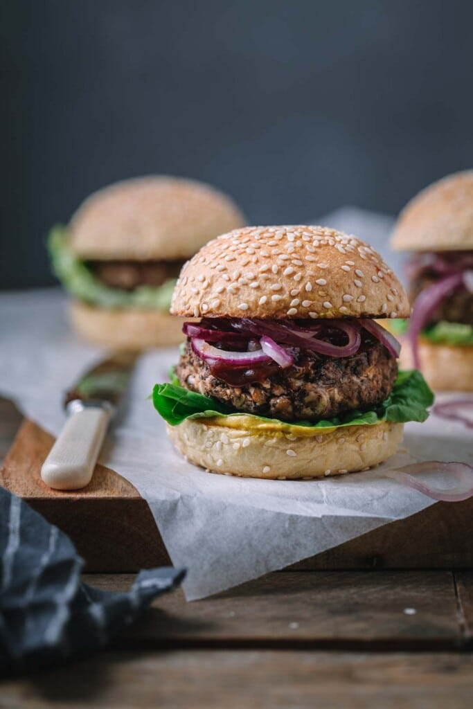 Front on image of a BBQ Vegan Black Bean Burger sitting on a rustic wooden board with two burgers in the background
