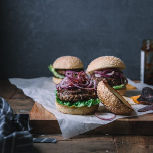 Black bean burgers in buns sitting on top of a wooden table