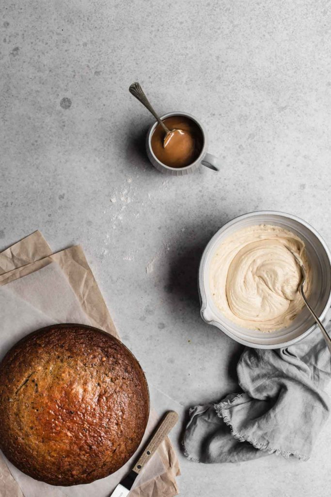 An overhead image of the freshly baked cake, the salted caramel frosting in a bowl and a cup of salted caramel. The cake is ready to decorate.