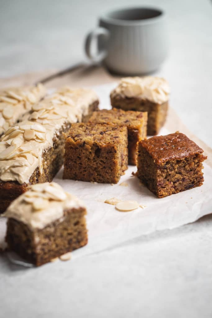 A frosted sticky date cake partially cut in to squares sitting on textured parchment paper with a cup in the background.