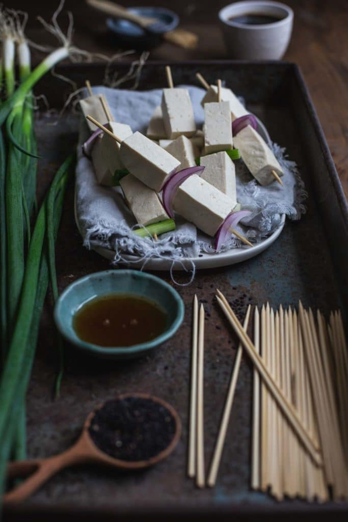 A plate of the pre-cooked tofu yakitori skewers, a pinch bowl of oil, a pot of dipping sauce and other ingredients sit inside a rustic tray ready to be grilled.