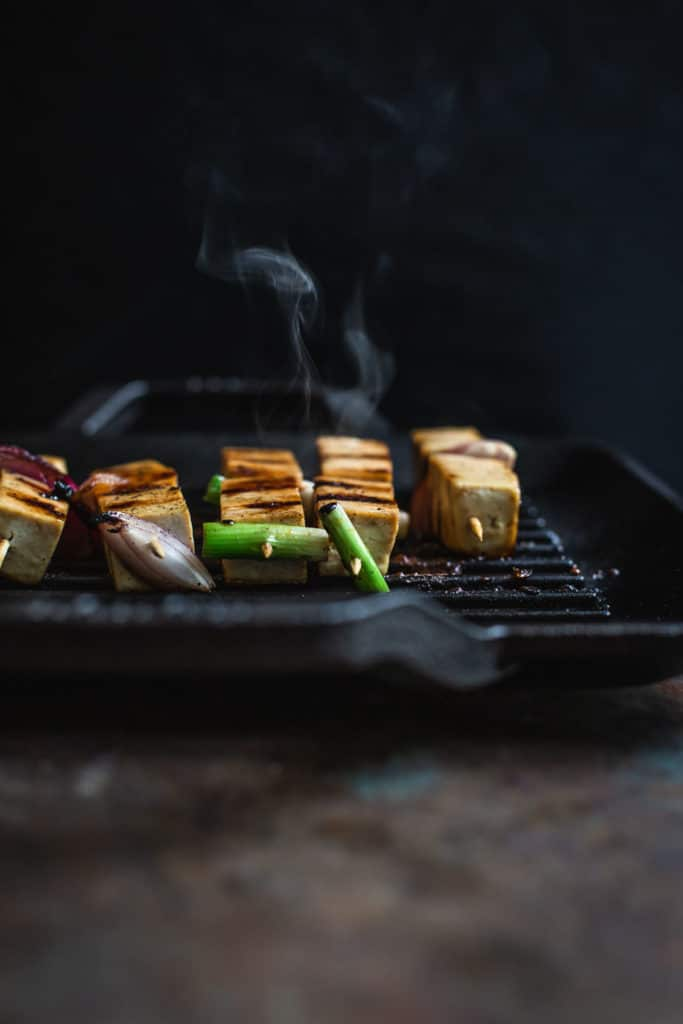 front on image of tofu yakitori grilling on a Lodge grill pan with smoke coming off the pan