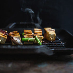 Tofu skewers cooking on a grill