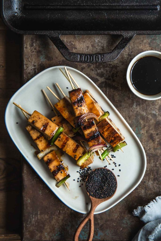 The finished grilled tofu yakitori skewers sit stacked on a rectangle white serving plate with a small bowl of dipping sauce nearby.