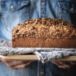 Close up image of hands holding banana bread on a board.