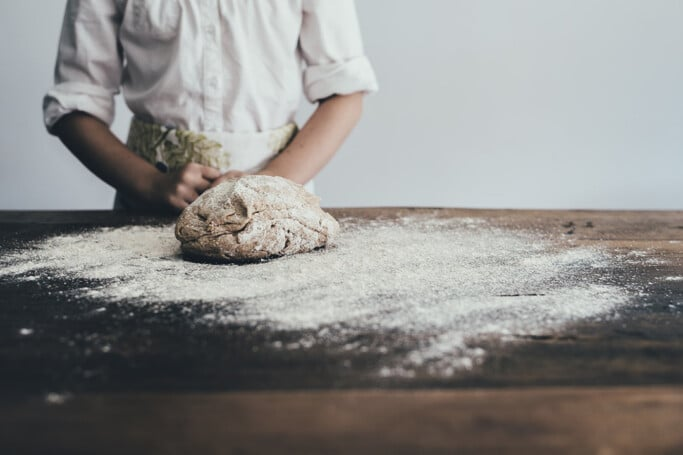A woman standing behind a table with dough and flour in front