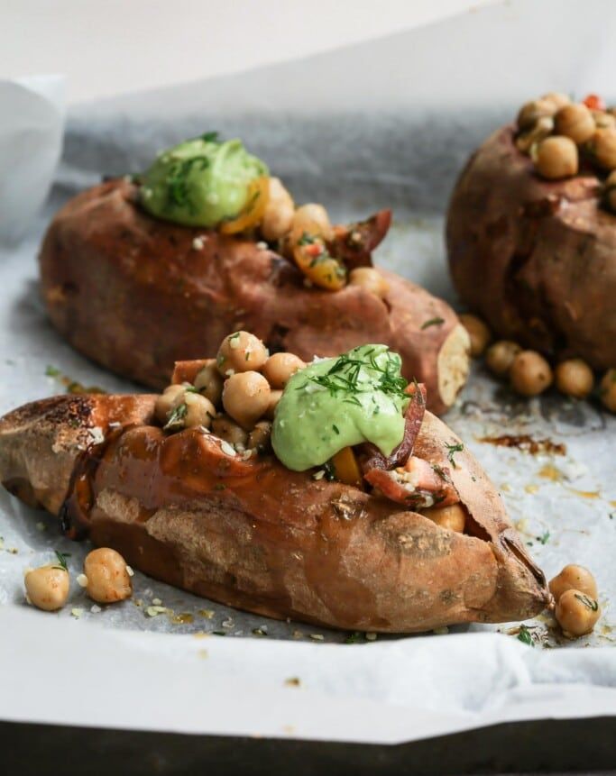 Three herbed chickpea stuffed sweet potatoes on a lined baking tray with the front potato in focus