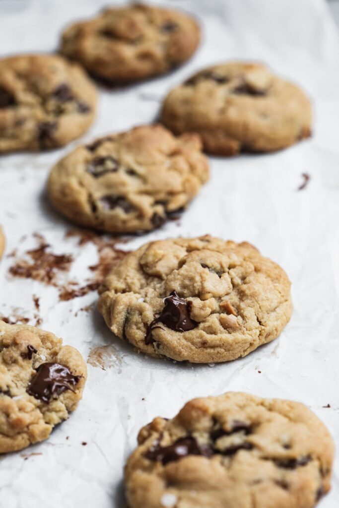 A tray lined with baking paper with freshly baked cookies