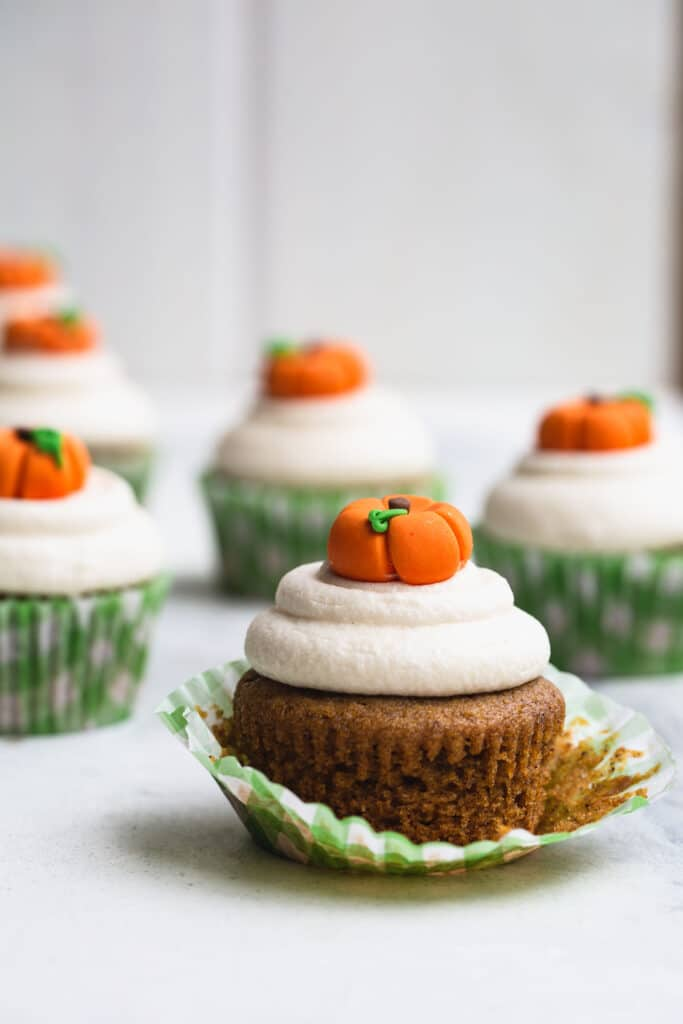 Pumpkin cupcakes with white frosting and a pumpkin topper on a white table
