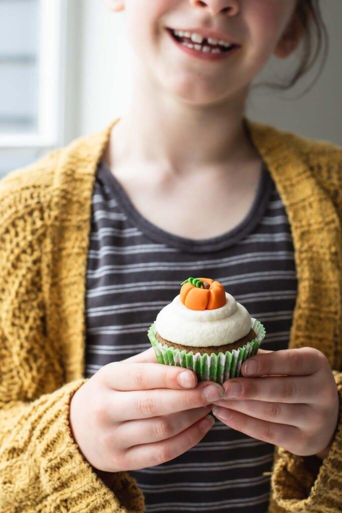 A little girl holding a cupcake