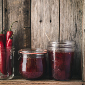 Jars of jam and chillies on a wooden shelf.