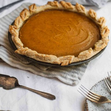A set table with a pumpkin pie in the middle.